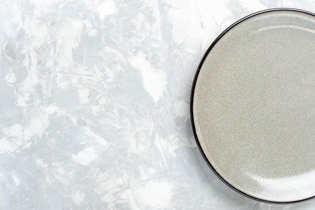 Vista superior do prato redondo vazio cinza na superfície branca