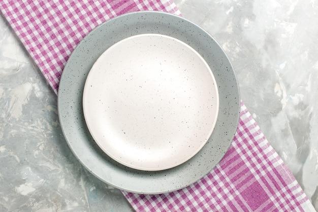 Vista superior do prato redondo vazio de cor cinza com placa branca na superfície cinza
