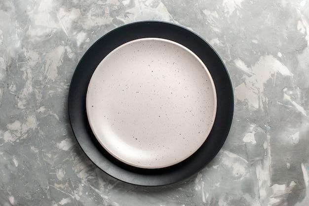 Vista superior do prato redondo vazio de cor preta com placa branca na superfície cinza