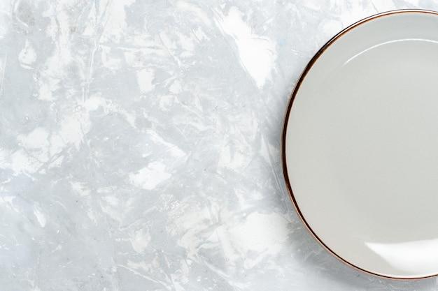 Vista superior do prato redondo vazio na mesa branca