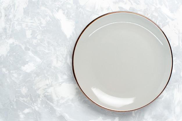 Vista superior do prato redondo vazio na superfície branca