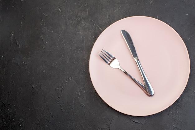 Vista superior do prato rosa com garfo e faca em superfície escura