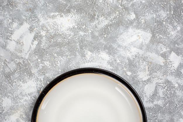 Vista superior do prato vazio em vidro branco feito na superfície branca