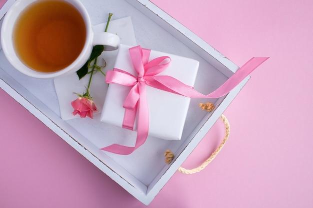 Vista superior do presente com laço rosa e chá na xícara na bandeja branca