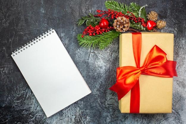 Vista superior do presente de ano novo com fita vermelha e enfeites de acessórios e caderno na superfície escura