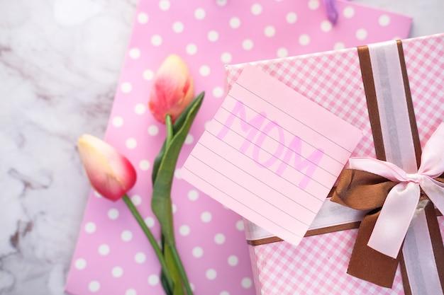 Vista superior do presente de dia das mães e flores na mesa.
