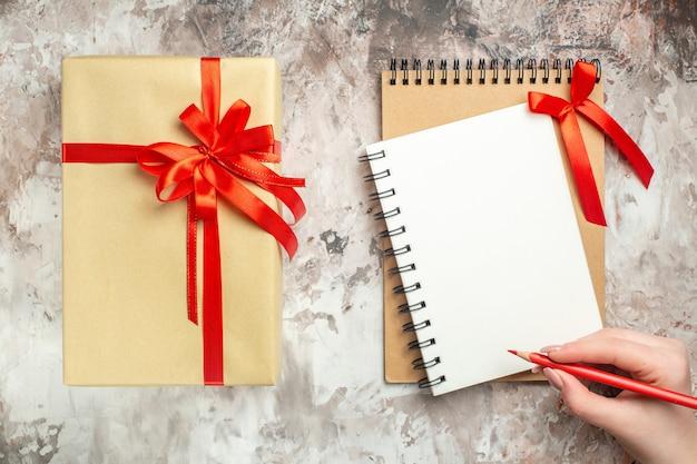 Vista superior do presente de natal amarrado com um laço vermelho na foto branca.
