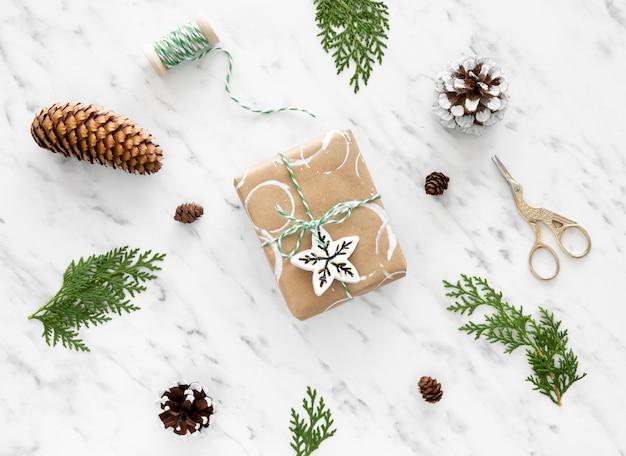 Vista superior do presente de natal com pinha e tesoura