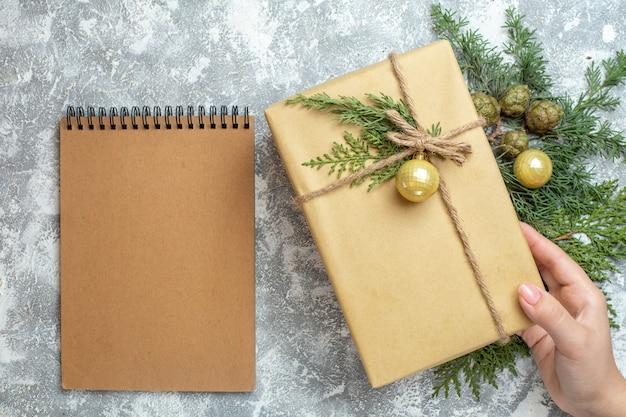 Vista superior do presente de natal com ramo verde e bloco de notas branco com foto colorida de natal presente de ano novo
