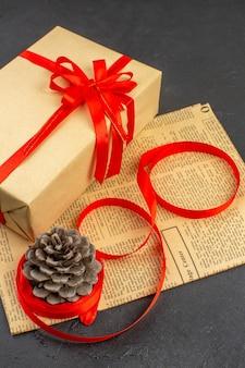 Vista superior do presente de natal em fita de papel pardo no jornal na superfície escura