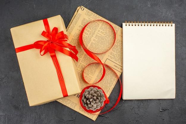 Vista superior do presente de natal em fita de papel pardo no jornal, um caderno na superfície escura