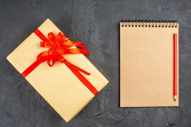 Vista superior do presente de natal em papel pardo amarrado com fita vermelha e caneta de caderno na superfície escura