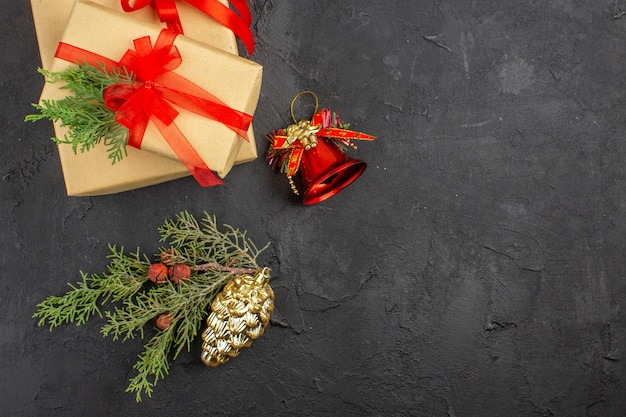 Vista superior do presente de natal em papel pardo amarrado com fita vermelha enfeites de árvore de natal na superfície escura