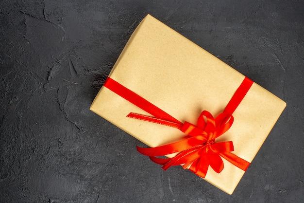 Vista superior do presente de natal em papel pardo amarrado com fita vermelha na superfície escura