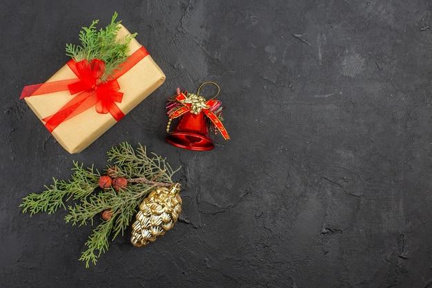 Vista superior do presente de natal em papel pardo amarrado com fita vermelha pingentes de árvore de natal na superfície escura