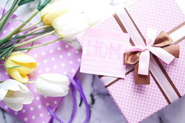 Vista superior do presente do dia das mães e flores na mesa