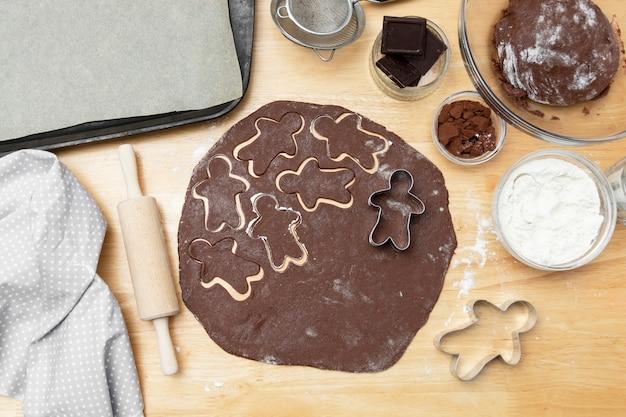 Vista superior do processo de cozimento, biscoitos festivos de gengibre de natal chocolate. cozinhar biscoitos de chocolate ou sobremesa.