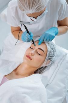 Vista superior do processo de remoção de toupeira na clínica de cosmetologia profissional