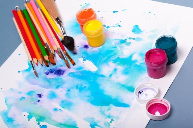 Vista superior do processo de trabalho de bloco de papel em aquarela, suprimentos para pintura em aquarela e pincéis