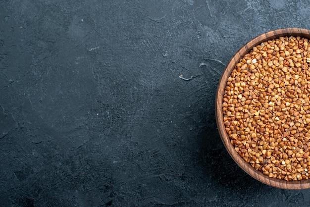 Vista superior do produto útil de trigo sarraceno cru dentro da placa no espaço escuro