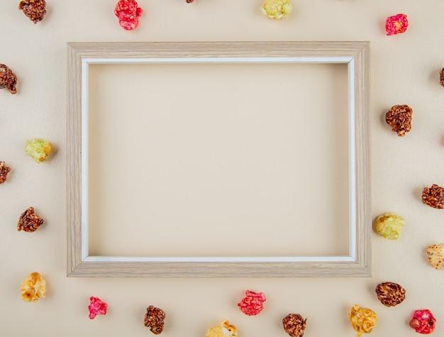 Vista superior do quadro branco com pipoca de skittles ao redor na superfície branca com espaço de cópia