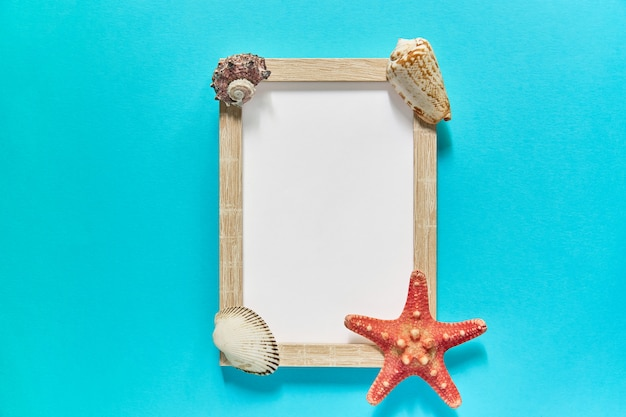 Vista superior do quadro com conchas e estrelas do mar em azul. conceito de férias de verão. configuração plana do mar