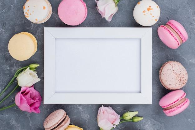 Vista superior do quadro com deliciosos macarons e rosas