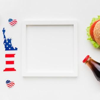 Vista superior do quadro com garrafa de hambúrguer e refrigerante ao lado da estátua da liberdade