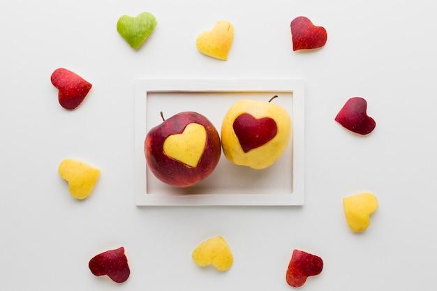Vista superior do quadro com maçãs e formas de coração de frutas