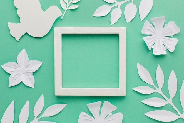 Vista superior do quadro com pomba de papel e folhas