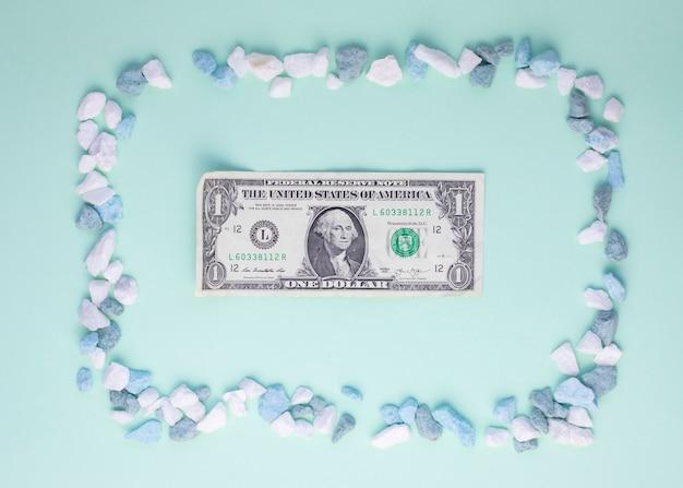 Vista superior do quadro de composição de seixos e nota de dólar em papelão verde