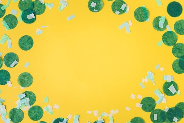 Vista superior do quadro de confete sobre fundo amarelo, com espaço de cópia