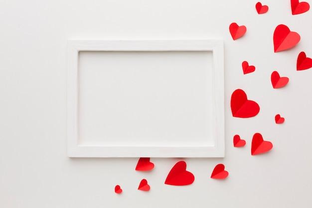 Vista superior do quadro e corações de papel para dia dos namorados