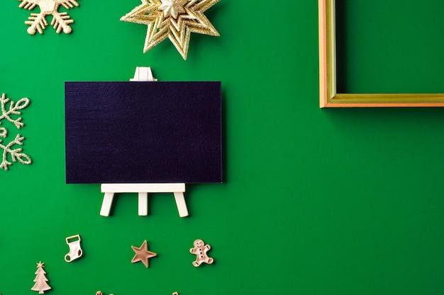 Vista superior do quadro-negro com coisas de ornamento de decoração de natal ouro e ano novo em verde