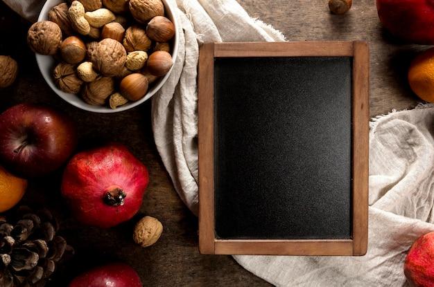 Vista superior do quadro-negro com frutas e nozes de outono
