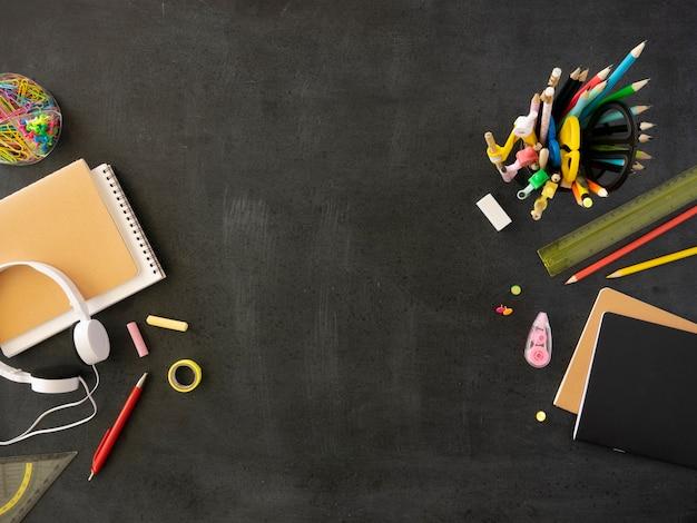 Vista superior do quadro negro emoldurado com materiais e artigos de papelaria do aluno