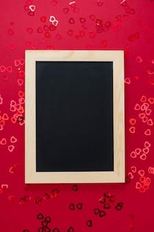Vista superior do quadro-negro vazio sobre fundo vermelho com confett brilhante.