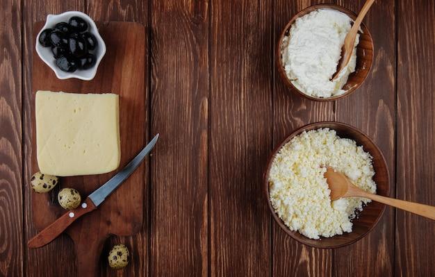 Vista superior do queijo cottage em bacias de madeira e um pedaço de queijo em uma tábua de madeira com uma faca de cozinha, ovos de codorna e azeitonas em conserva na mesa rústica