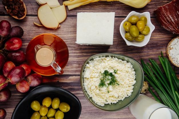 Vista superior do queijo cottage em uma tigela com queijo feta, mel em uma garrafa de vidro, uvas doces e azeitonas em conserva na madeira rústica
