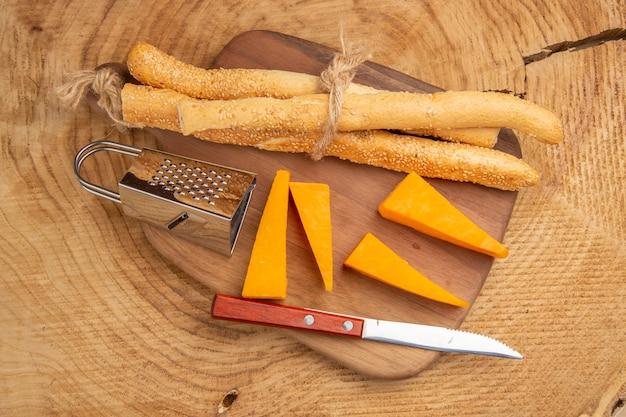 Vista superior do queijo e da faca de pão pequeno ralador na tábua