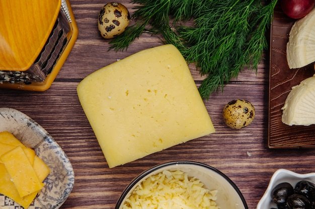 Vista superior do queijo holandês com ovos de codorna endro e queijo ralado em uma tigela de madeira rústica