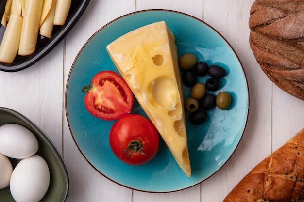 Vista superior do queijo maasdam com tomates e azeitonas em um prato com ovos de galinha e um pedaço de pão preto e branco em um prato branco