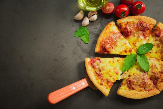 Vista superior do queijo quente da pizza, queijo saboroso da pizza no preto.