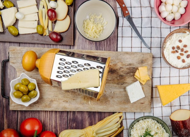 Vista superior do ralador com queijo e azeitonas em conserva em uma tábua de madeira em rústico