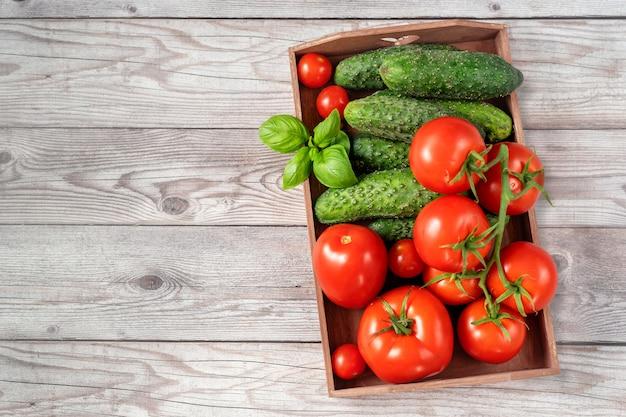 Vista superior do recipiente de madeira cheio de tomates colhidos maduros, vermelhos e suculentos.