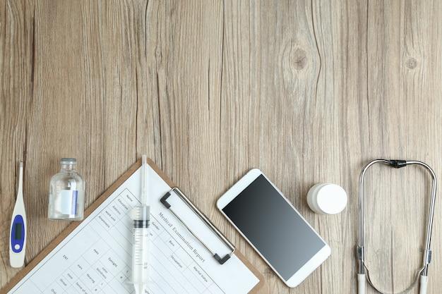 Vista superior do relatório de exame médico, celular e equipamentos médicos na mesa de madeira