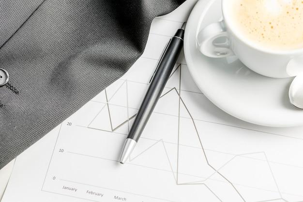 Vista superior do relatório financeiro anual de negócios com café e caneta