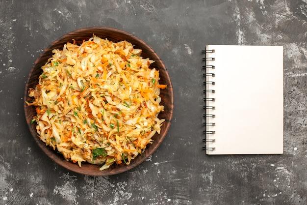 Vista superior do repolho com cenouras tigela de repolho com cenouras ao lado do caderno