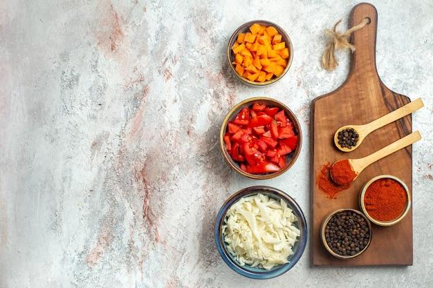 Vista superior do repolho fresco fatiado com tomate e pimenta no espaço em branco