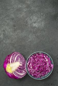 Vista superior do repolho roxo fatiado dentro do prato em fundo escuro